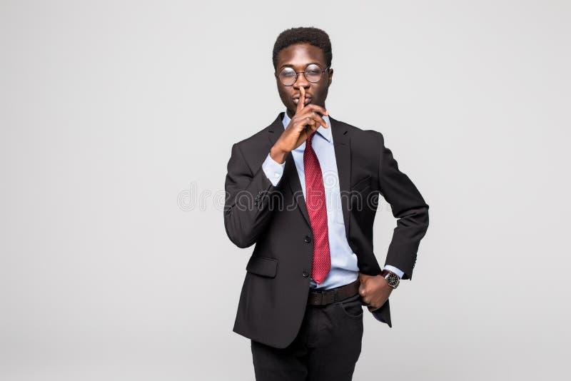 Homme d'affaires africain sérieux de portrait de plan rapproché le jeune plaçant le doigt sur des lèvres indiquant, shhh, soit tr photo stock