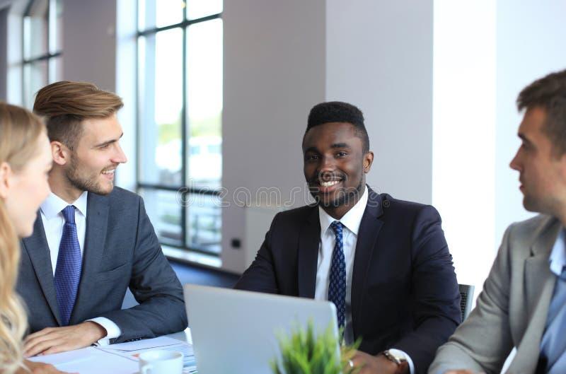 Homme d'affaires africain sûr de sourire lors d'une réunion avec collègues assis à une table de conférence dans le bureau images stock