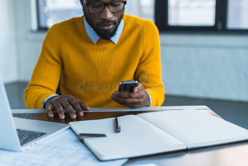 homme d'affaires d'afro-américain à l'aide du smartphone photos stock