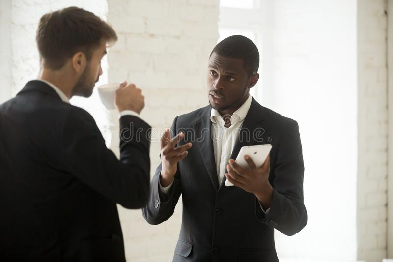 Homme d'affaires d'afro-américain discutant le nouvel APP avec p caucasien images libres de droits