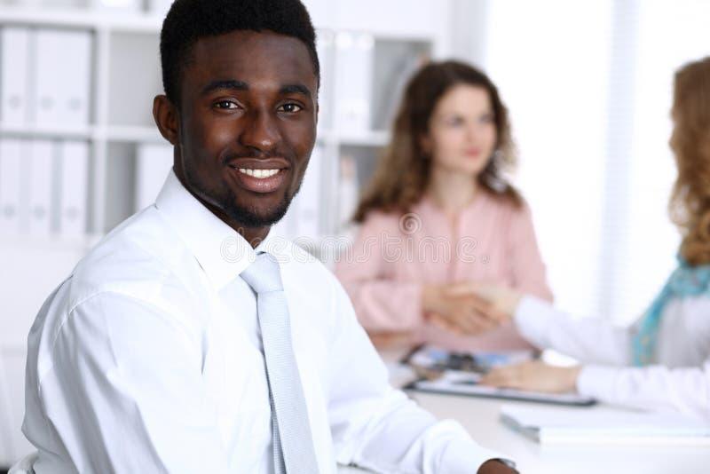 Homme d'affaires d'afro-américain lors de la réunion dans le bureau, coloré dans le blanc Groupe ethnique multi d'hommes d'affair photo libre de droits