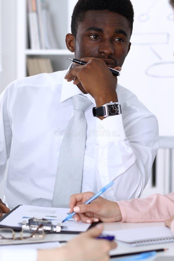 Homme d'affaires d'afro-américain lors de la réunion dans le bureau, coloré dans le blanc Groupe ethnique multi d'hommes d'affair photos libres de droits