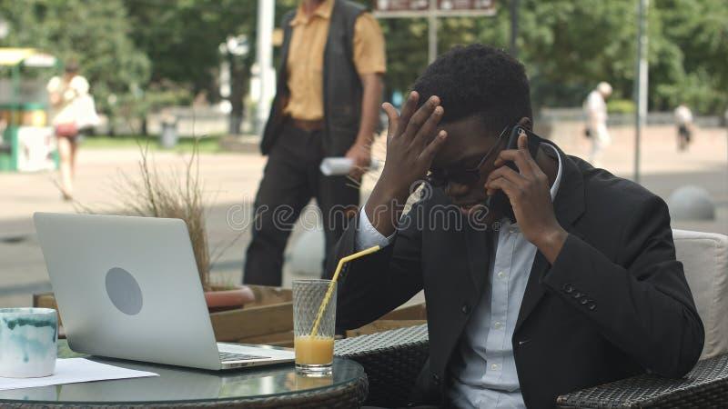 Homme d'affaires afro-américain négociant par le téléphone, défendant ses intérêts et avis images stock