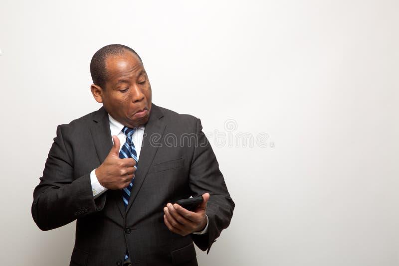Homme d'affaires d'afro-américain renonçant au pouce par l'intermédiaire du téléphone images stock
