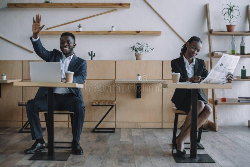 homme d'affaires d'afro-américain travaillant sur l'ordinateur portable tandis que journal de lecture de femme d'affaires images libres de droits