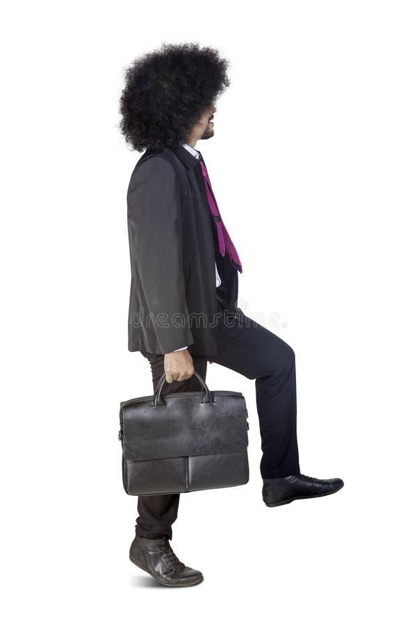 Homme d'affaires d'Afro posant pour faire un pas vers le haut sur le studio photos libres de droits