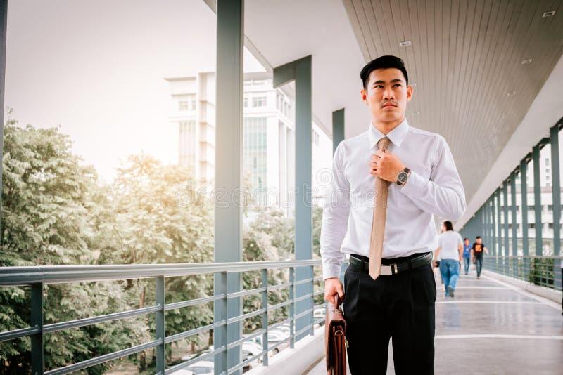 Homme d'affaires ajustant la cravate avant temps de travail image stock