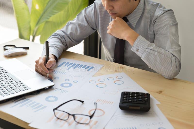 Homme d'affaires analysant des diagrammes et des graphiques avec le compu moderne d'ordinateur portable image libre de droits
