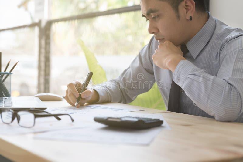 Homme d'affaires analysant des diagrammes et des graphiques avec le compu moderne d'ordinateur portable photographie stock