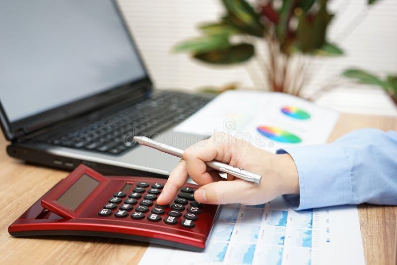 Homme d'affaires analysant des données commerciales avec la calculatrice, ordinateur portable, repor photographie stock