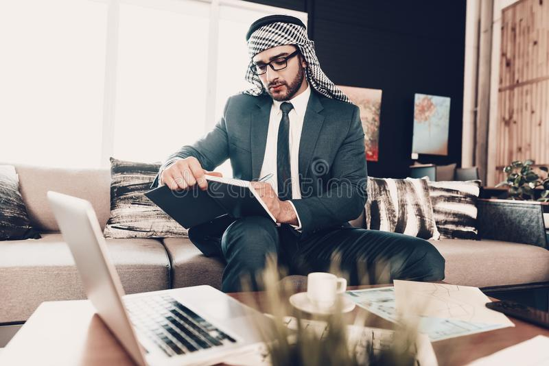 Homme d'affaires arabe prenant des notes au carnet image stock