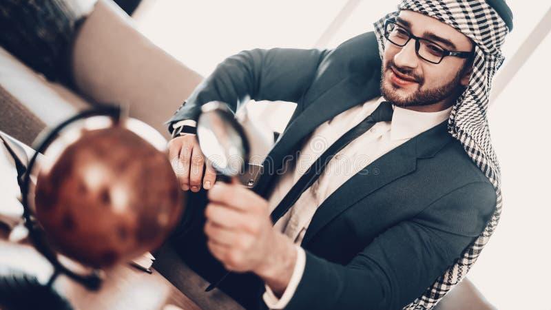 Homme d'affaires arabe regardant le globe avec la loupe photos libres de droits