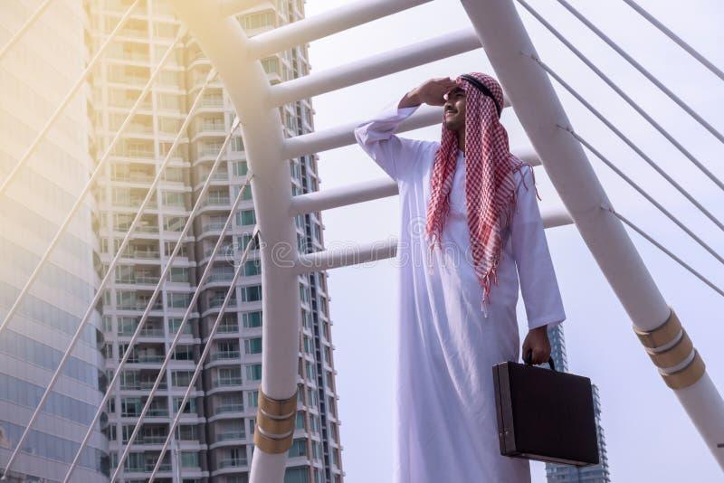Homme d'affaires Arabe sûr tenant et regardant le backg de ville images libres de droits