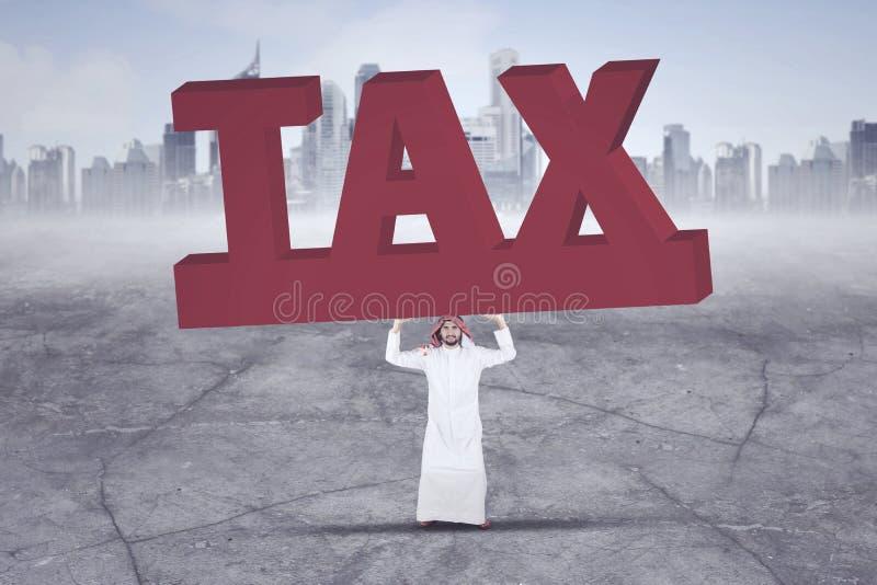 Homme d'affaires Arabe soulevant un grand et lourd mot d'impôt avec des gratte-ciel à l'arrière-plan image stock