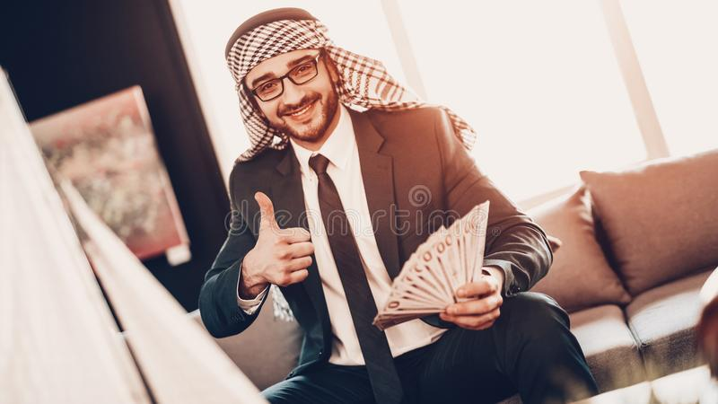 Homme d'affaires arabe tenant des pouces d'argent et d'exposition  photo stock