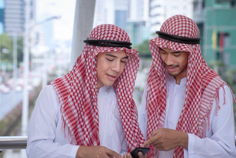 Homme d'affaires Arabe utilisant le téléphone portable avec le colleauge pour le presenti images stock