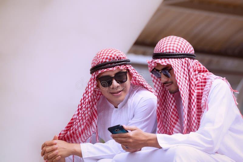 Homme d'affaires Arabe utilisant le téléphone portable avec le colleauge pour le presenti images libres de droits
