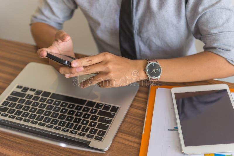 Homme d'affaires asiatique à l'aide du smartphone, de l'ordinateur portable et du comprimé photographie stock