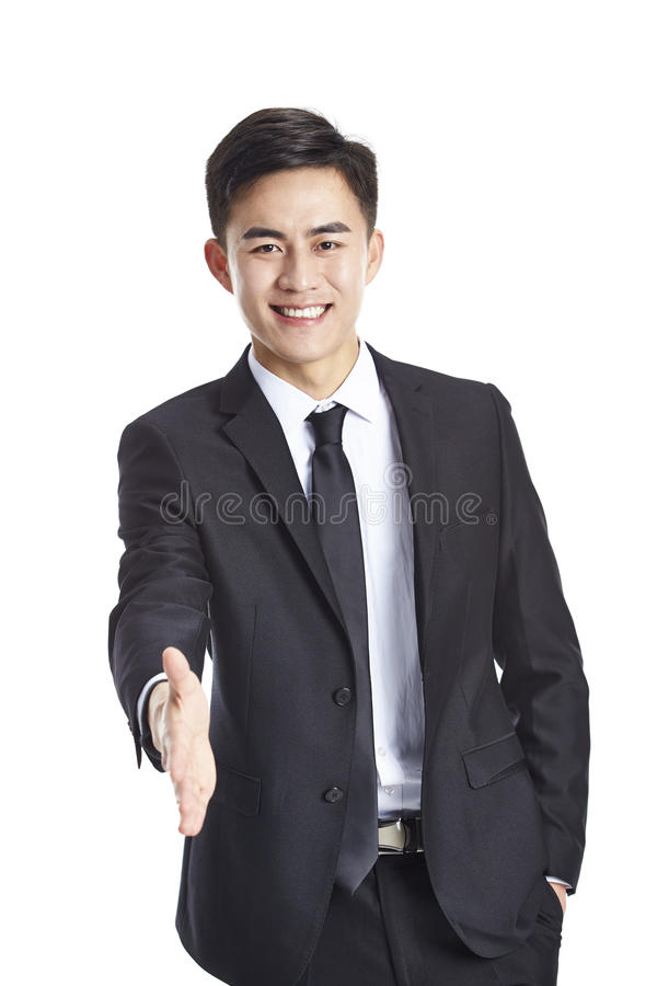 Homme d'affaires asiatique atteignant pour la poignée de main image stock