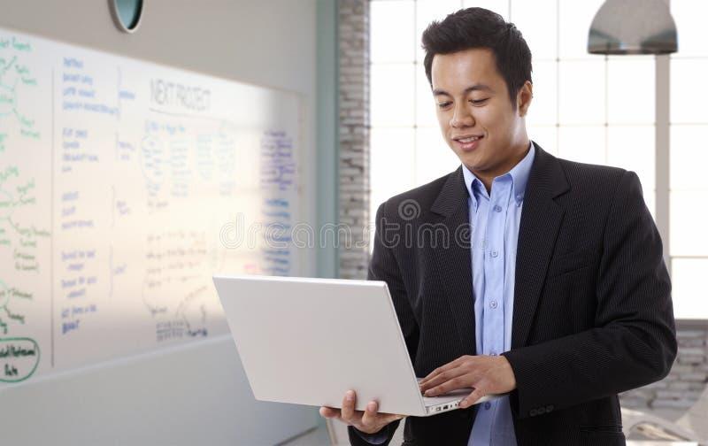 Homme d'affaires asiatique avec l'ordinateur portable dans la salle du conseil d'administration image libre de droits