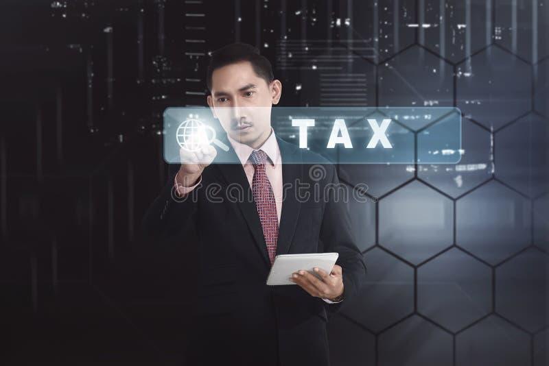 Homme d'affaires asiatique bel avec l'impôt émouvant de tablette mais photographie stock