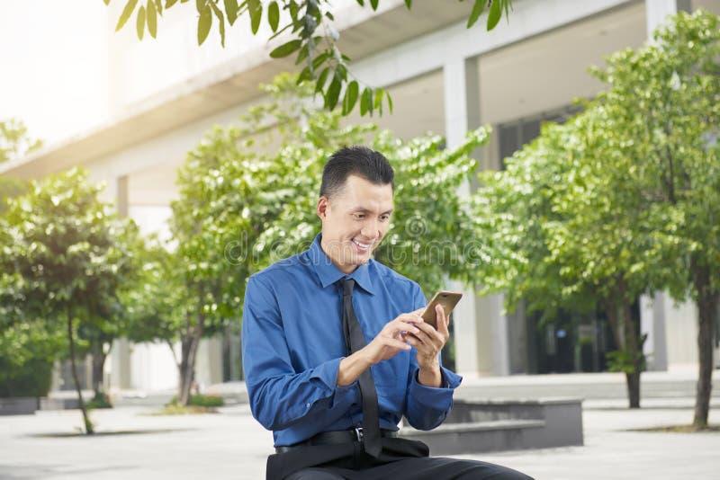 Homme d'affaires asiatique bel utilisant le téléphone portable images libres de droits