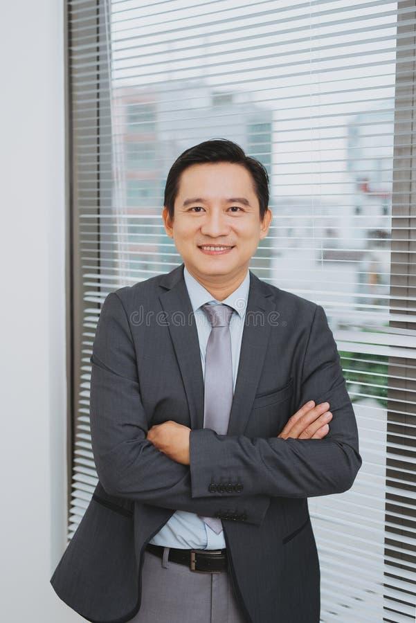 Homme d'affaires asiatique de sourire se tenant prêt la fenêtre images stock