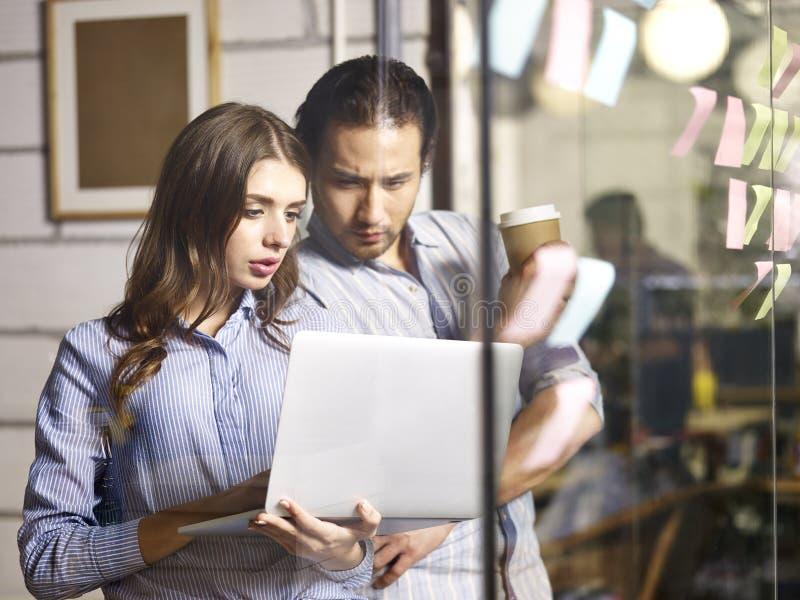 Homme d'affaires asiatique et femme d'affaires caucasienne travaillant ensemble photo libre de droits
