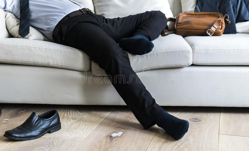 Homme d'affaires asiatique faisant la pause s'étendant sur le divan image stock