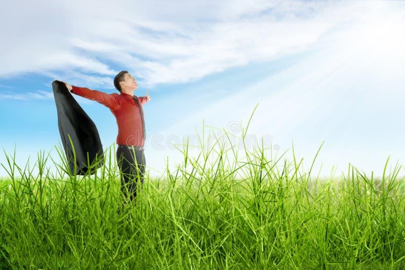 Homme d'affaires asiatique heureux avec la participation de bras ouverte une position de costume sur l'herbe photos stock
