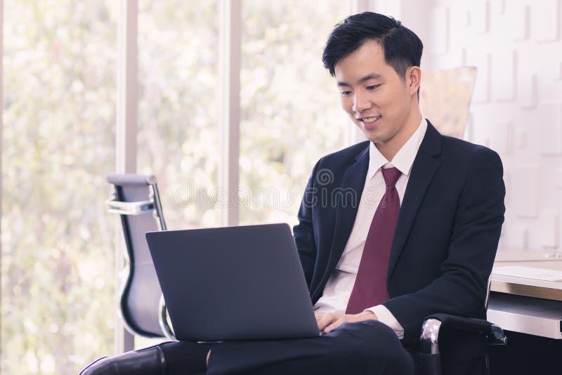 Homme d'affaires asiatique ? l'aide de l'ordinateur portable dans le bureau images stock