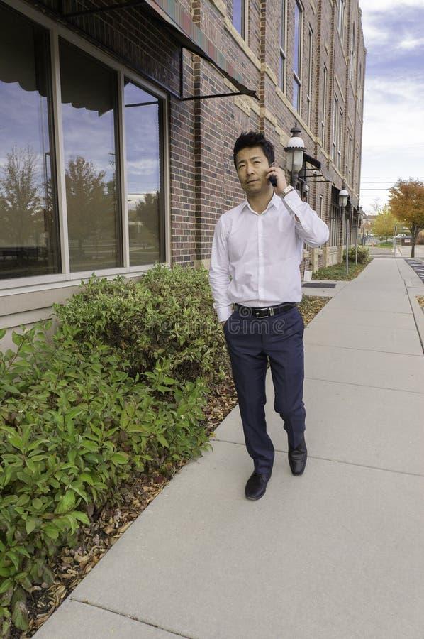 Homme d'affaires asiatique marchant tout en parlant au téléphone portable dehors photos libres de droits