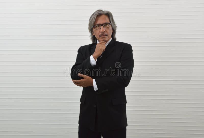 Homme d'affaires asiatique plus âgé futé dans le costume noir et lunettes tenant sa main sur son menton au-dessus du fond blanc d images stock