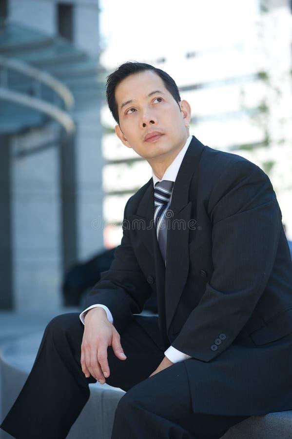Homme d'affaires asiatique posant dehors image stock