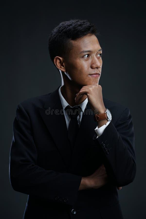 Homme d'affaires asiatique réfléchi avec la main sur Chin image stock
