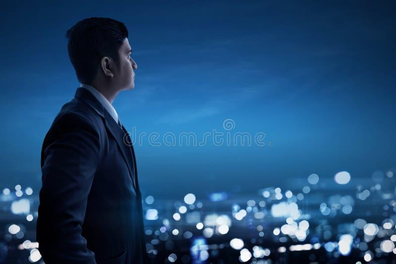 Homme d'affaires asiatique regardant la ville de nuit image libre de droits