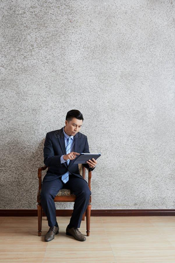Homme d'affaires asiatique s'asseyant et travaillant sur le PC de comprimé images stock