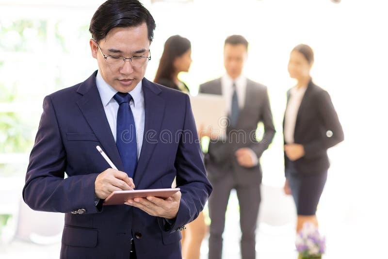 Homme d'affaires asiatique travaillant avec l'équipe photographie stock libre de droits