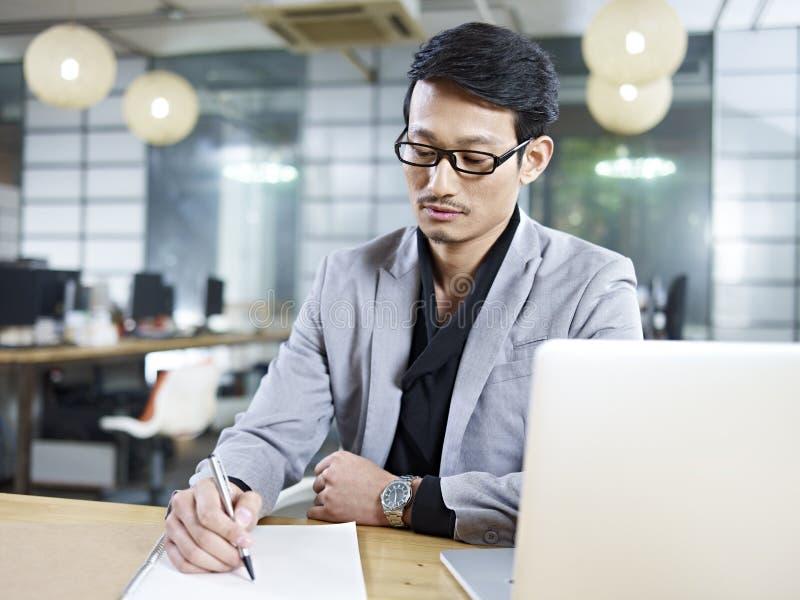Homme d'affaires asiatique travaillant dans le bureau photo stock