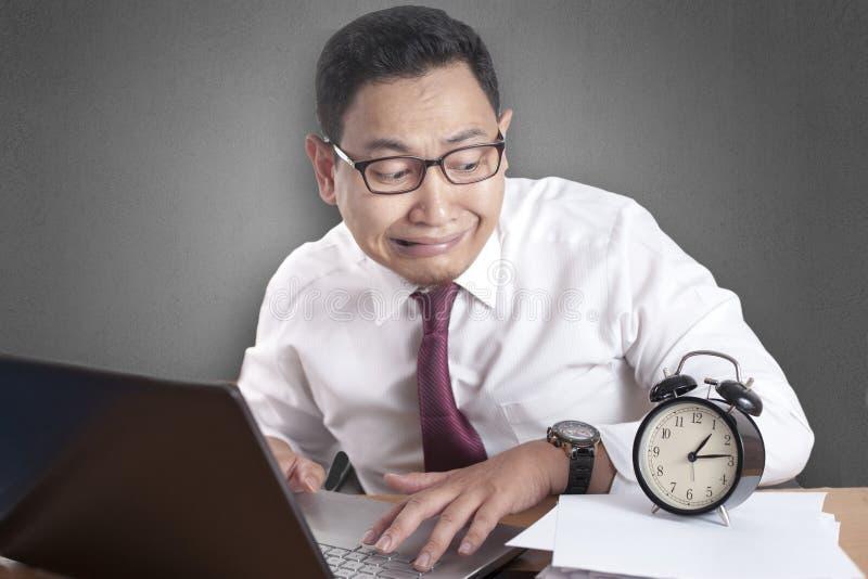 Homme d'affaires asiatique Worried par temps, effort de date-butoir de travail photographie stock