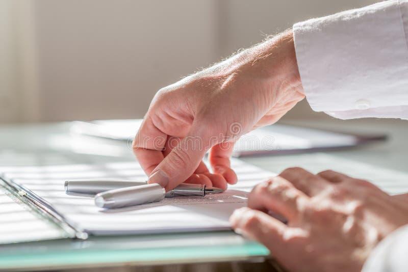 Homme d'affaires atteignant pour son stylo-plume photos stock