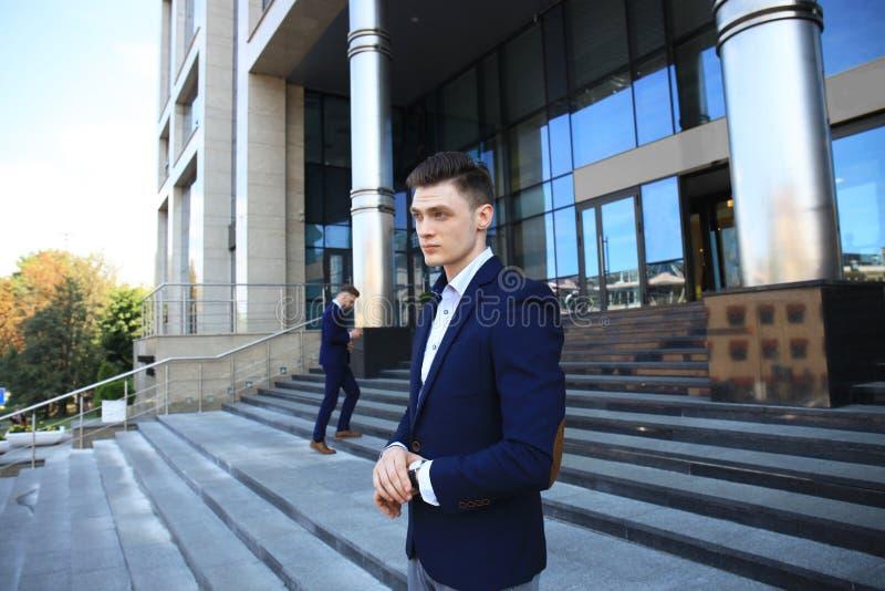 Homme d'affaires attendant son collègue en dehors de regarder la montre photo libre de droits