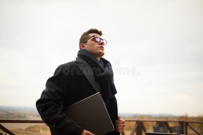 Homme d'affaires attirant bel utilisant un ordinateur portable sur la terrasse de bureau L'homme élégant en verres enduisent et é images libres de droits