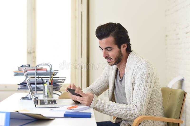 Homme d'affaires attirant d'indépendant de style d'étudiant ou de hippie travaillant avec l'ordinateur portable et le téléphone p photographie stock