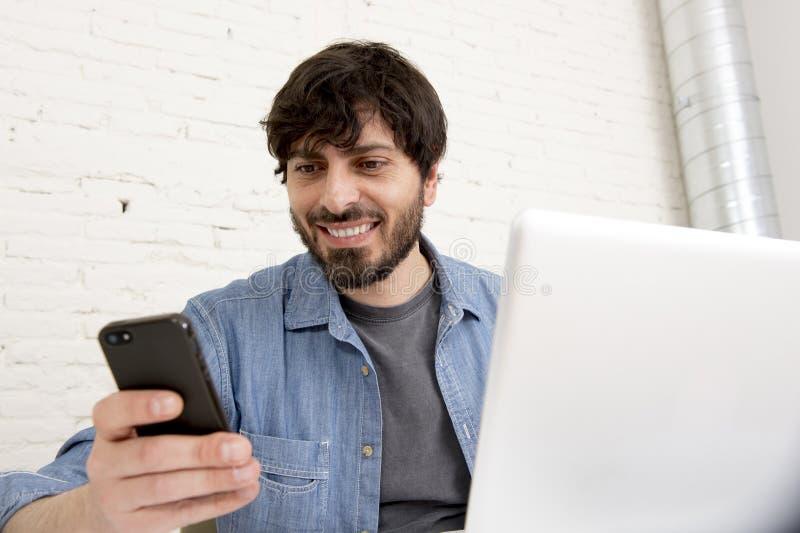 Homme d'affaires attirant hispanique de hippie travaillant à la maison le bureau utilisant le téléphone portable photo libre de droits