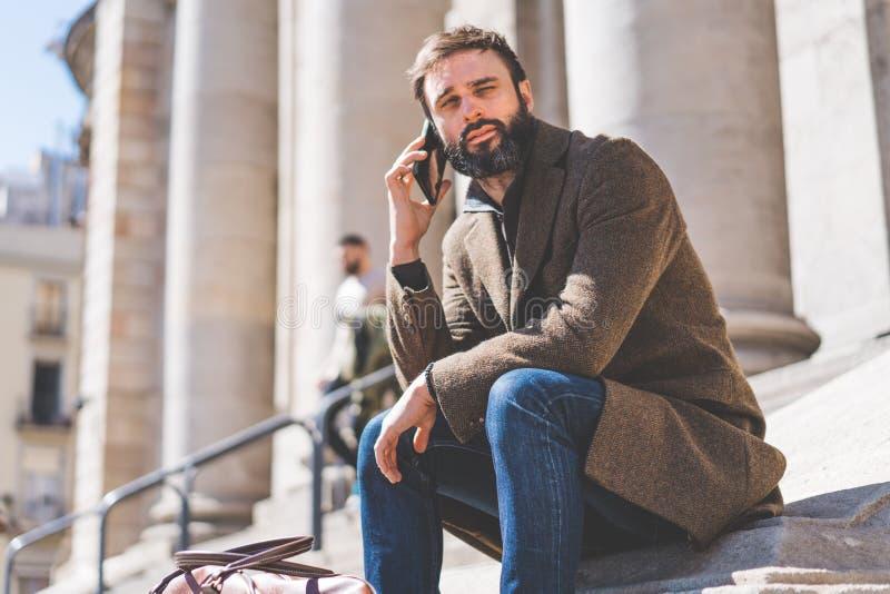Homme d'affaires attirant parlant à un téléphone portable Entrepreneur professionnel occasionnel à l'aide du smartphone dehors photos libres de droits