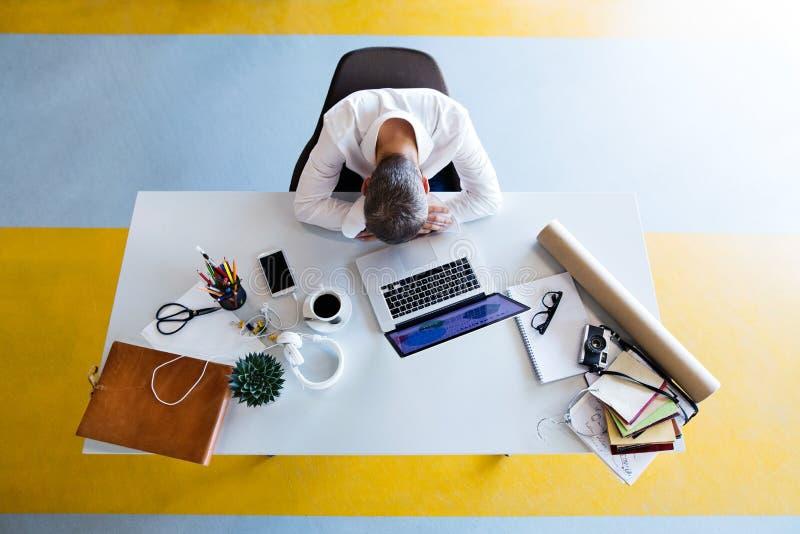 Homme d'affaires au bureau avec l'ordinateur portable dans son bureau image libre de droits