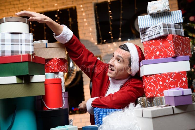 Homme d'affaires au bureau sur le ` s Ève de nouvelle année Il utilise le costume de Santa Claus Autour de lui beaucoup de cadeau photographie stock
