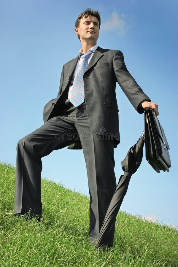 Homme d'affaires au pré photo stock