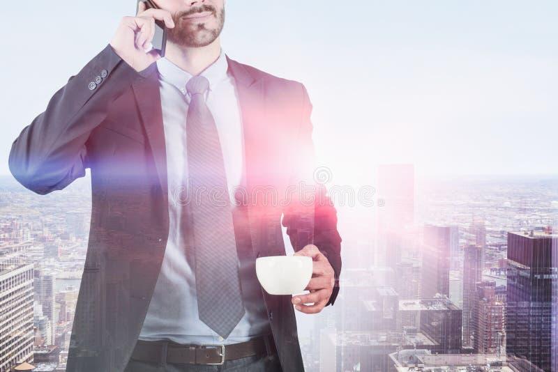 Homme d'affaires au téléphone avec du café dans la ville images libres de droits